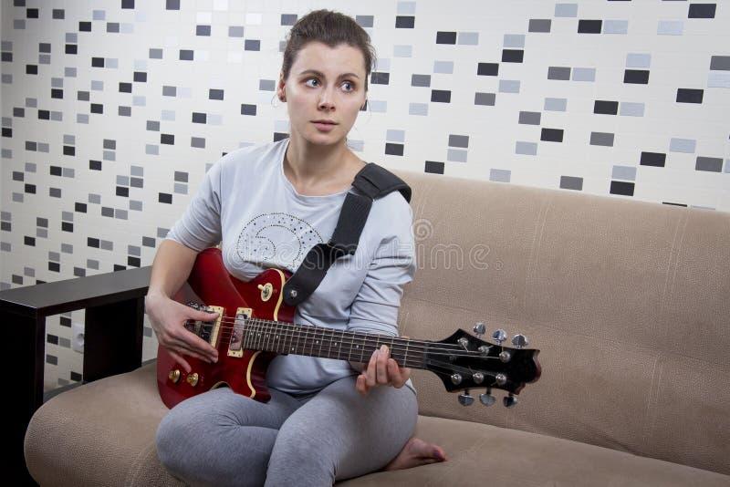 La chica joven está tocando la guitarra eléctrica en casa Guitarra roja en manos de la mujer hermosa en el apartamento imagen de archivo libre de regalías
