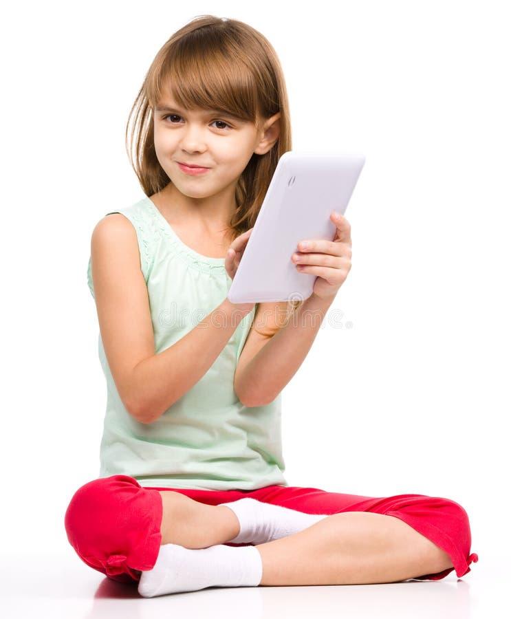 La chica joven está utilizando la tableta fotografía de archivo libre de regalías