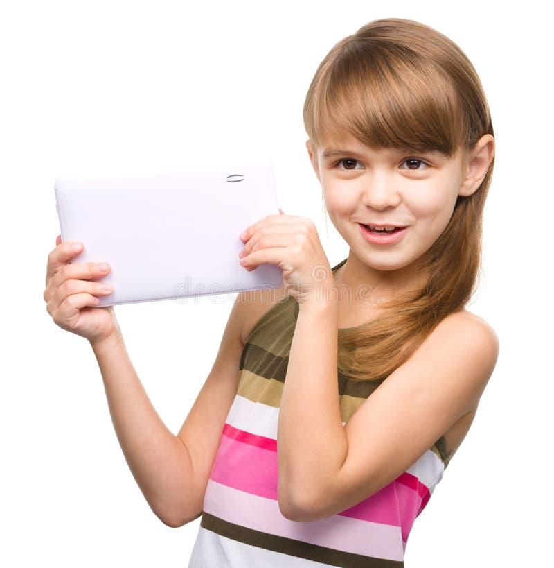La chica joven está utilizando la tableta imagen de archivo
