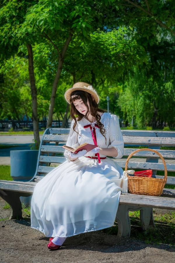 La chica joven est? leyendo un libro que se sienta en un banco imagen de archivo