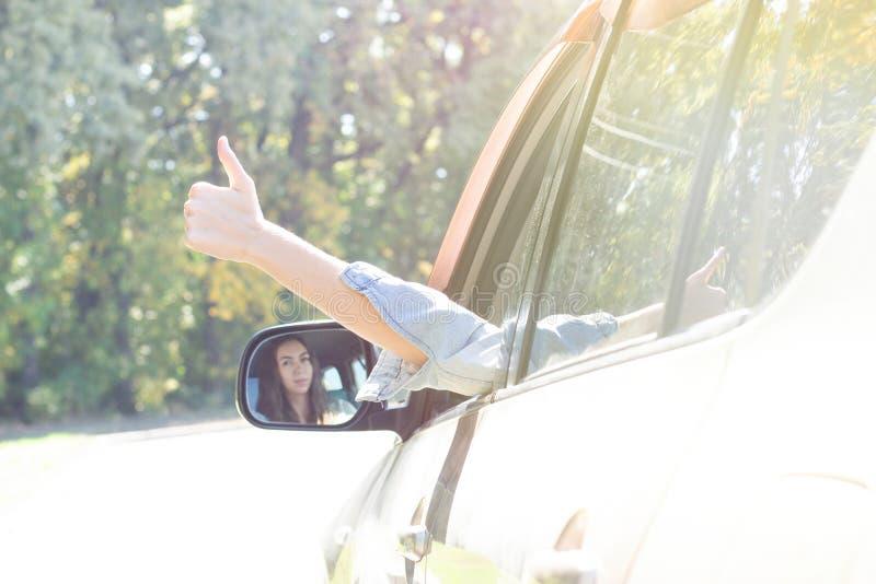 La chica joven feliz joven conduce un coche los controles que ella distribuye de la ventana. La señora chofer disfruta conduciend fotografía de archivo libre de regalías