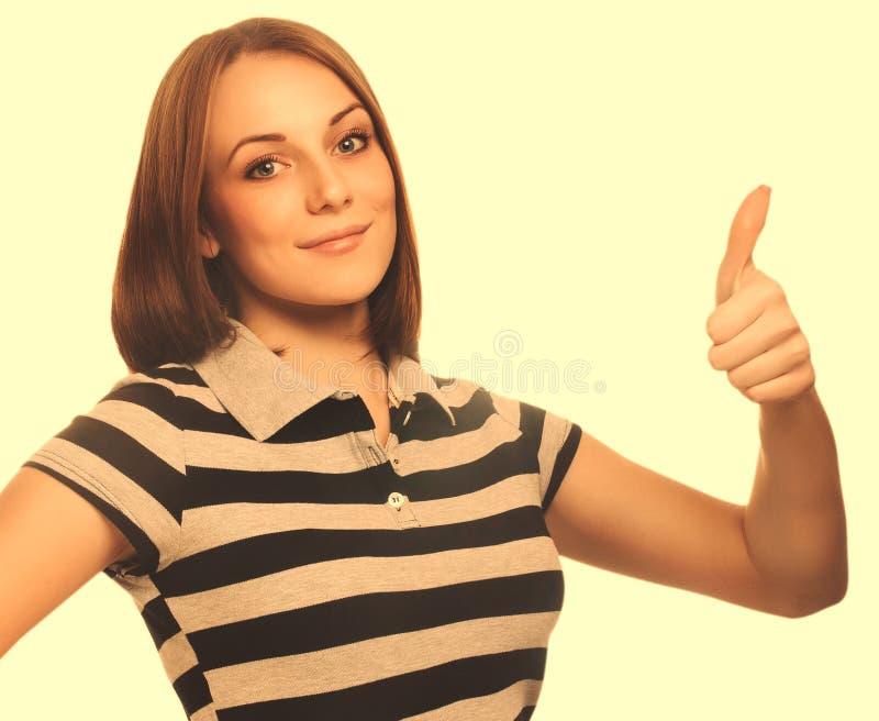 La chica joven feliz de la mujer del retrato muestra los pulgares del signo positivo sí, foto de archivo