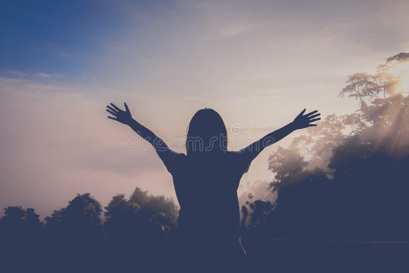 La chica joven feliz goza el hacer excursionismo Mire la primera luz del sol de la ma?ana en la monta?a Sienta restaurado y activ imagen de archivo libre de regalías