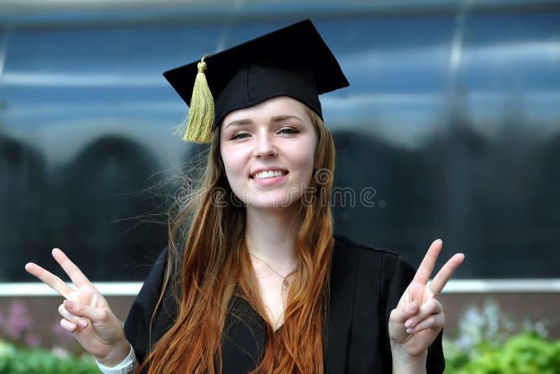 La chica joven graduada con el pelo rojo vestido en capa y el casquillo académico cuadrado sonríen en campus universitario fotos de archivo