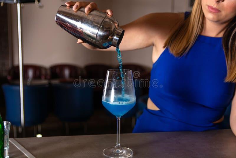 La chica joven hace un cóctel azul de la laguna en la barra en el restaurante imagen de archivo libre de regalías