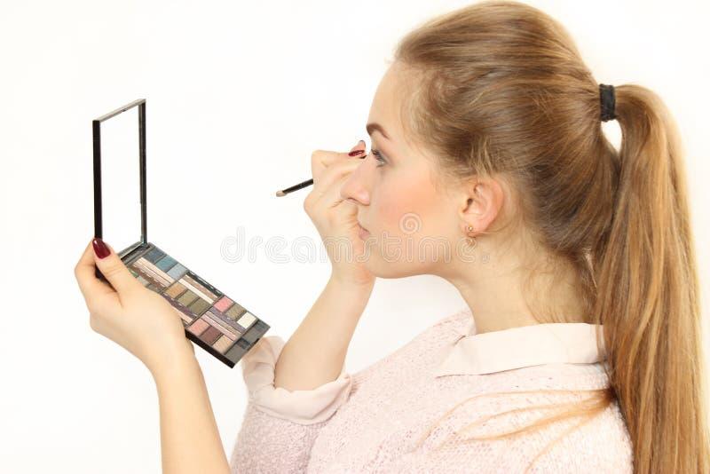 La chica joven hace un maquillaje delante de un pequeño espejo cosmético foto de archivo