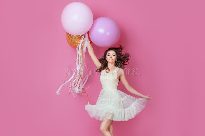 La chica joven hermosa alegre en vestido con la chispa y el helio rosado hincha disfrutando del baile del photoshoot del cumpleañ imagenes de archivo