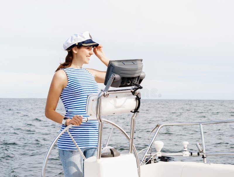 La chica joven hermosa, atractiva pilota un mar Mediterráneo del barco fotografía de archivo libre de regalías