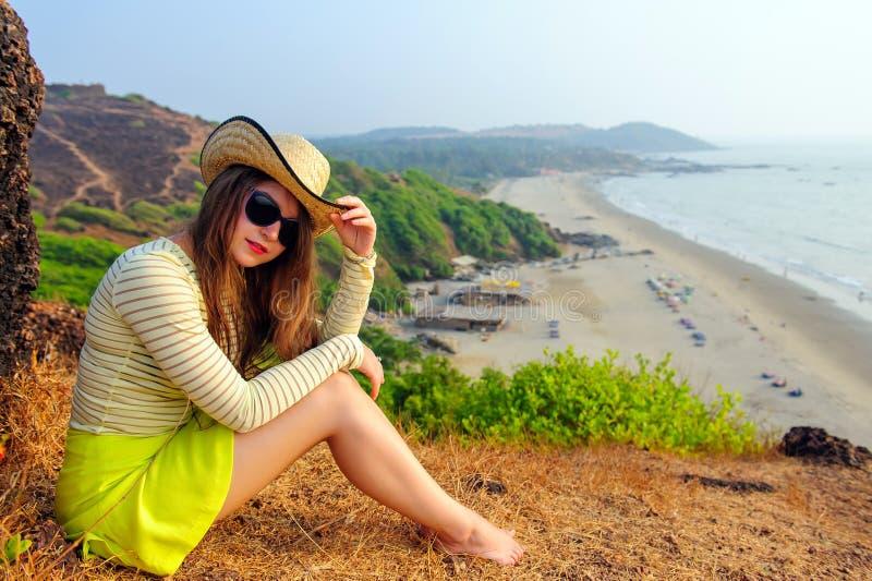 La chica joven hermosa con el pelo largo en sombrero de paja, vidrios oscuros y falda amarilla corta se sienta en el top contra l imagen de archivo