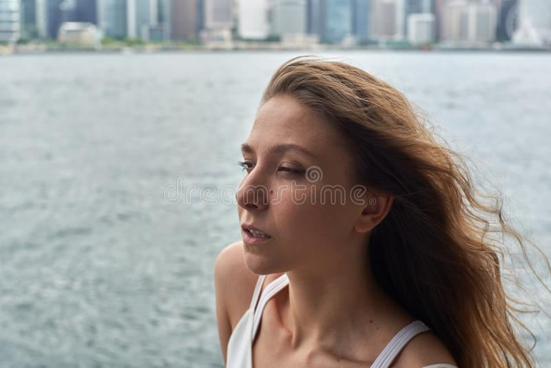 La chica joven hermosa con el pelo marrón y los ojos impresionantes en el océano varan en la metrópoli Hong Kong fotografía de archivo libre de regalías
