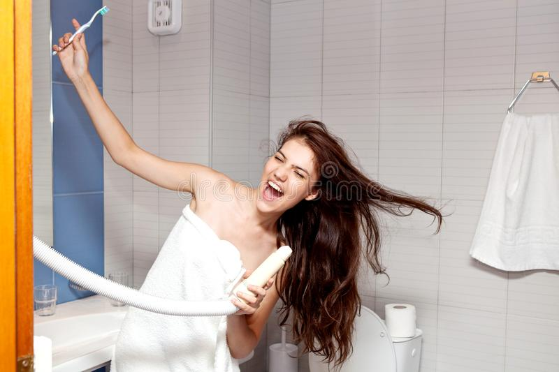 La chica joven hermosa con el pelo negro largo y en una toalla blanca el cabello seco con un hairdryer foto de archivo