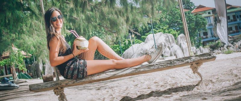 La chica joven hermosa disfruta de un oscilación y bebe el coco imagen de archivo