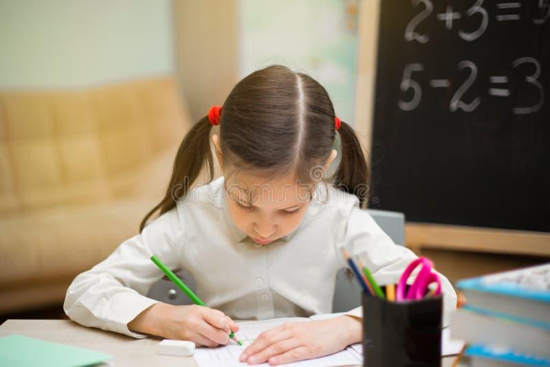La chica joven hermosa está enseñando en casa en la pizarra Educación casera preescolar imagen de archivo libre de regalías