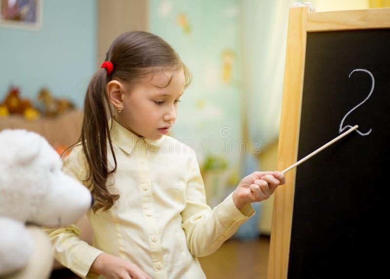 La chica joven hermosa está enseñando a los juguetes en casa en la pizarra Educación casera preescolar imagen de archivo libre de regalías