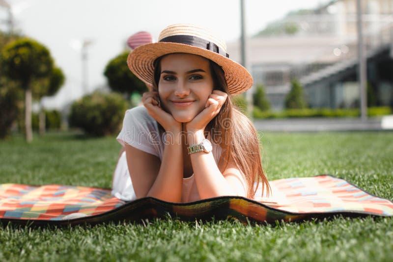 La chica joven hermosa está poniendo en la manta en el parque y la sonrisa fotos de archivo libres de regalías