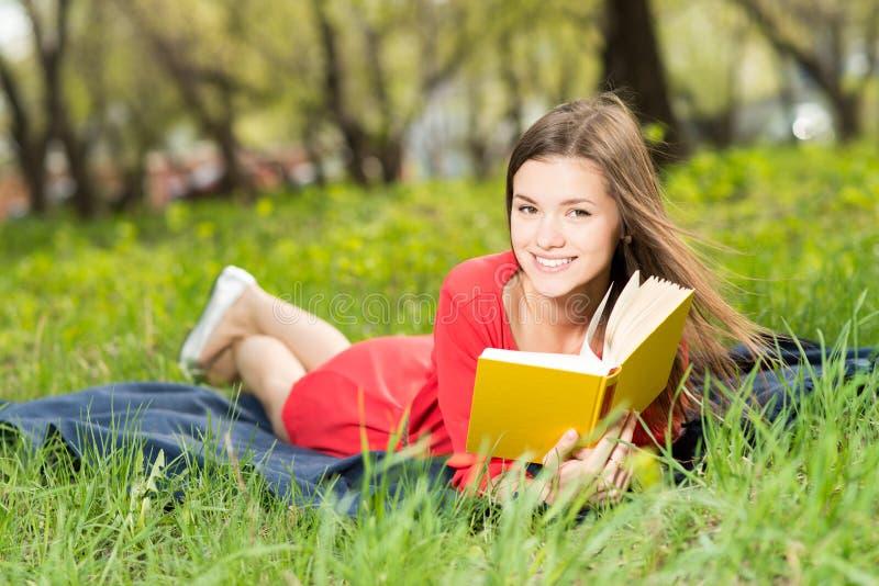 La chica joven hermosa lee el libro en parque fotografía de archivo libre de regalías