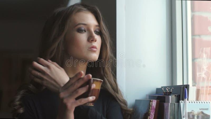 La chica joven hermosa mira a través de la ventana y bebe el coffe almacen de video