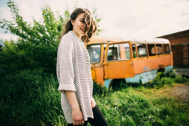 La chica joven hermosa presenta cerca del coche retro imagen de archivo
