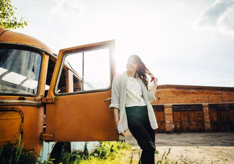 La chica joven hermosa presenta cerca del coche retro imagenes de archivo