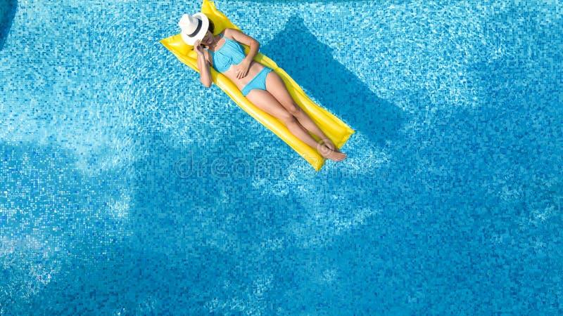 La chica joven hermosa que se relaja en la piscina, nadadas en el colch?n inflable y se divierte en agua el vacaciones de familia fotografía de archivo libre de regalías