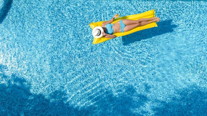 La chica joven hermosa que se relaja en la piscina, nadadas en el colch?n inflable y se divierte en agua el vacaciones de familia imagen de archivo libre de regalías