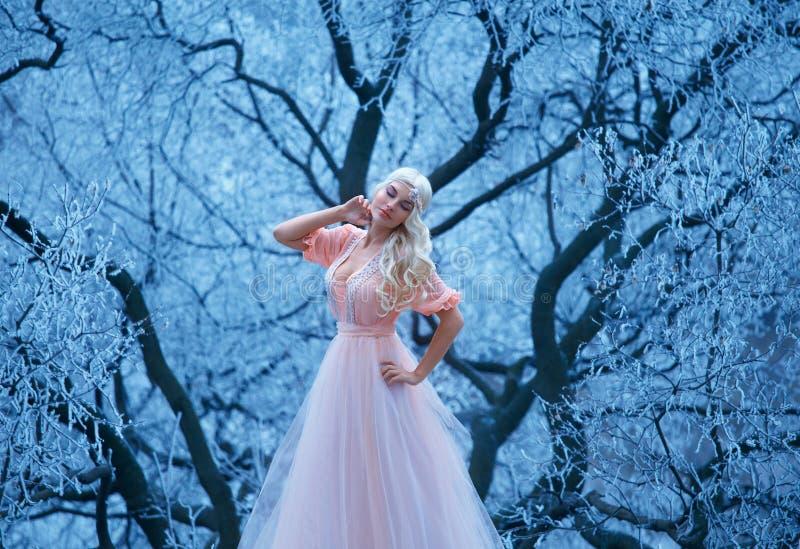 La chica joven hermosa se coloca en árboles nevosos del fondo fotografía de archivo
