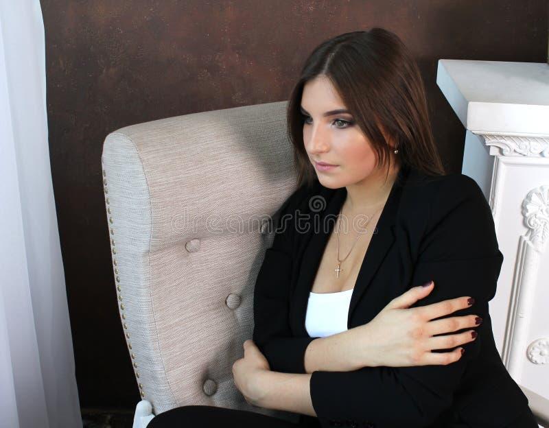La chica joven hermosa se sienta en una silla y abraza sus brazos imagen de archivo libre de regalías