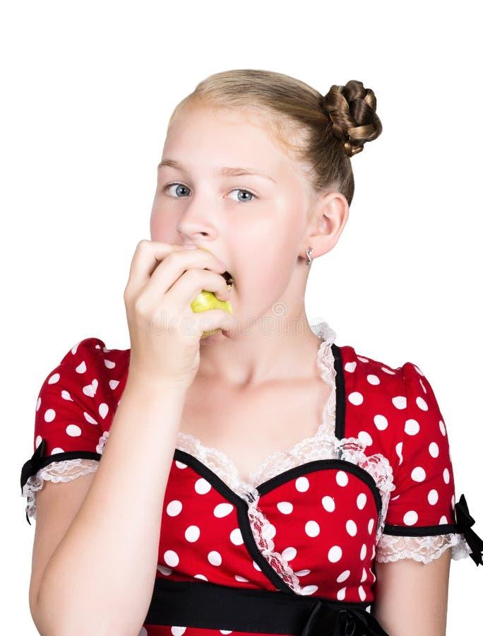 La chica joven hermosa se vistió en un vestido rojo con los lunares blancos que comía una manzana comida sana - concepto fuerte d foto de archivo libre de regalías