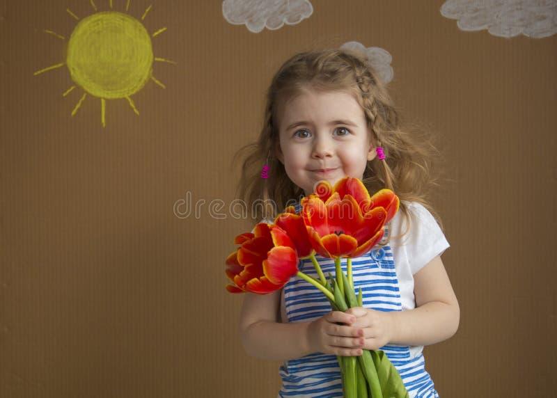 La chica joven hermosa sonriente con los tulipanes en la primavera, copia el espacio, el 8 de marzo día internacional del ` s de  foto de archivo libre de regalías