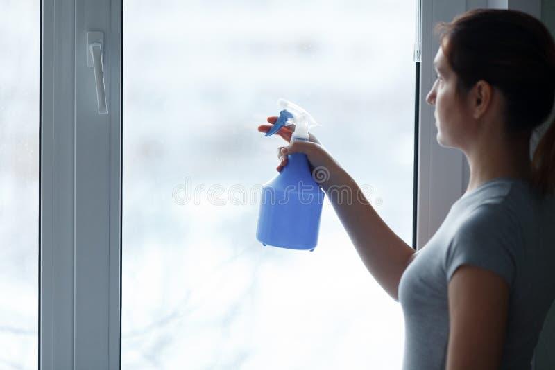 La chica joven lava y limpia cuidadosamente una ventana fotos de archivo