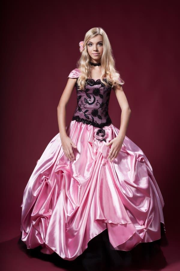 La chica joven le gusta una muñeca de Barbie imagen de archivo