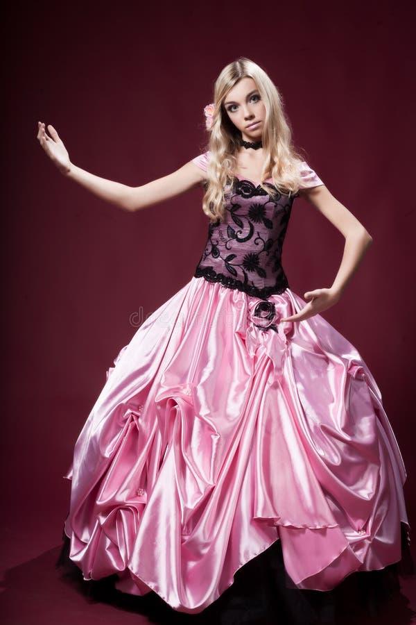 La chica joven le gusta una muñeca de Barbie foto de archivo