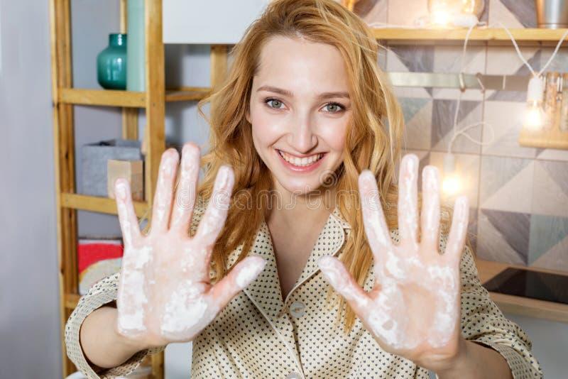 La chica joven le muestra las manos en harina imágenes de archivo libres de regalías