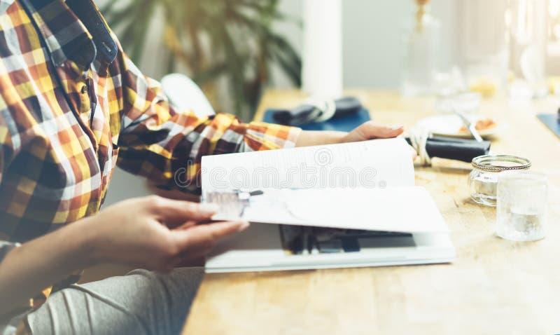 La chica joven lee el libro durante el desayuno y el café, manos femeninas cercanas encima de mover de un tirón a través de las p foto de archivo libre de regalías