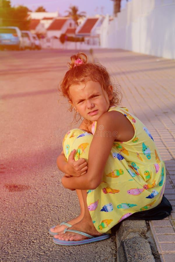 La chica joven linda que parece triste, solo, asustado, abuso, desamparados se está sentando en la tierra Tiempo de la tarde Luz  imagen de archivo
