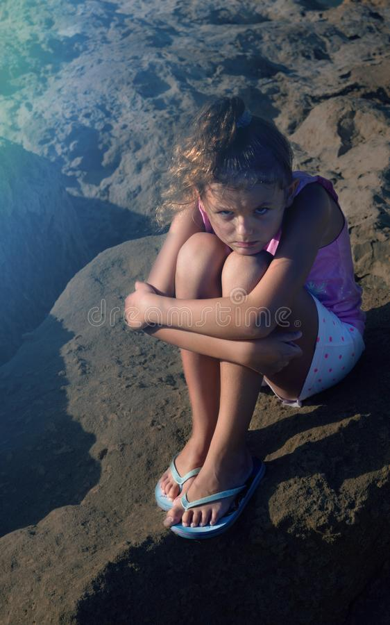 La chica joven linda que parece triste, solo, asustado, abuso, desamparados se está sentando en la tierra Tiempo de la tarde Luz  imagen de archivo libre de regalías