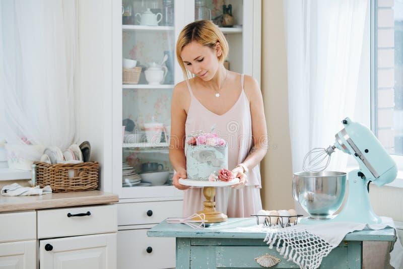 La chica joven lleva a cabo un soporte con una torta hermosa fotos de archivo libres de regalías