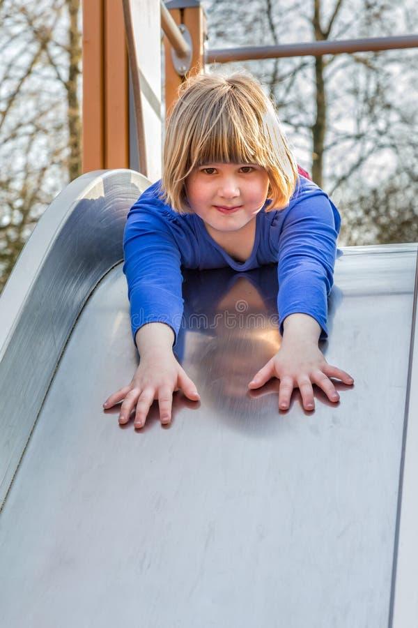 La chica joven miente adelante en diapositiva fotografía de archivo libre de regalías