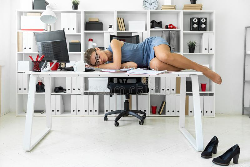 La chica joven miente con los ojos cerrados en documentos en el escritorio en oficina fotografía de archivo libre de regalías
