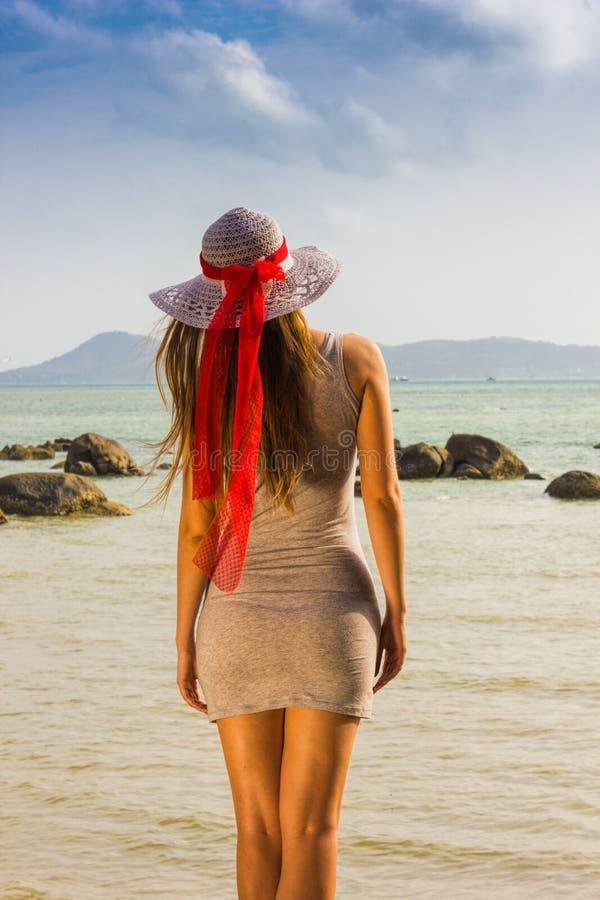 La chica joven mira al mar en el sombrero imagenes de archivo