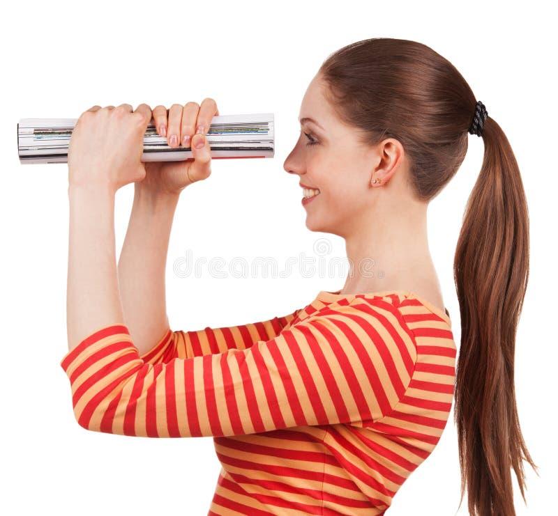 La muchacha mira en la revista doblada, como un telescopio imagen de archivo