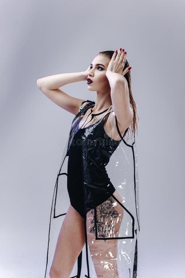 La chica joven misteriosa con la barra de labios oscura y el pelo mojado vestidos en traje que nada negro y capa de lluvia transp imagen de archivo