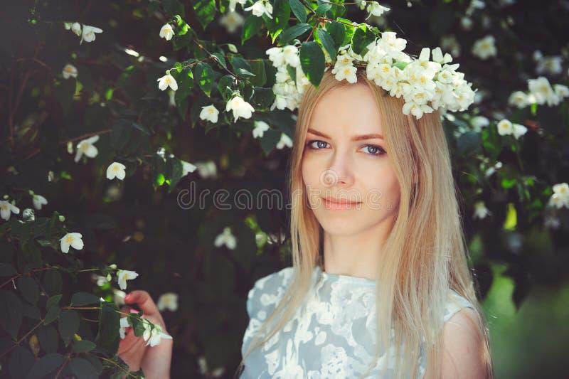 La chica joven modesta atractiva con el blonde con las flores del jazmín enrruella en el pelo largo principal y el maquillaje nat fotografía de archivo