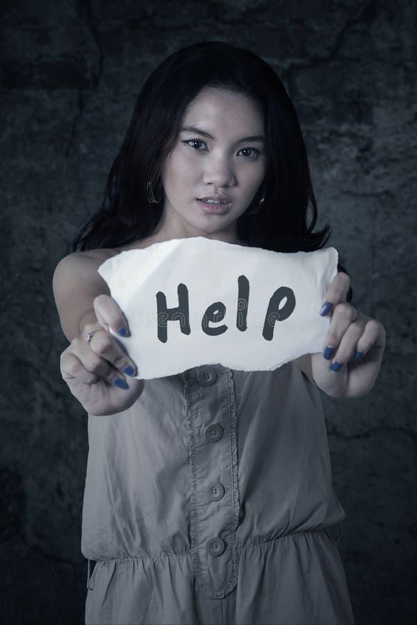 La chica joven muestra ayuda de la palabra fotos de archivo