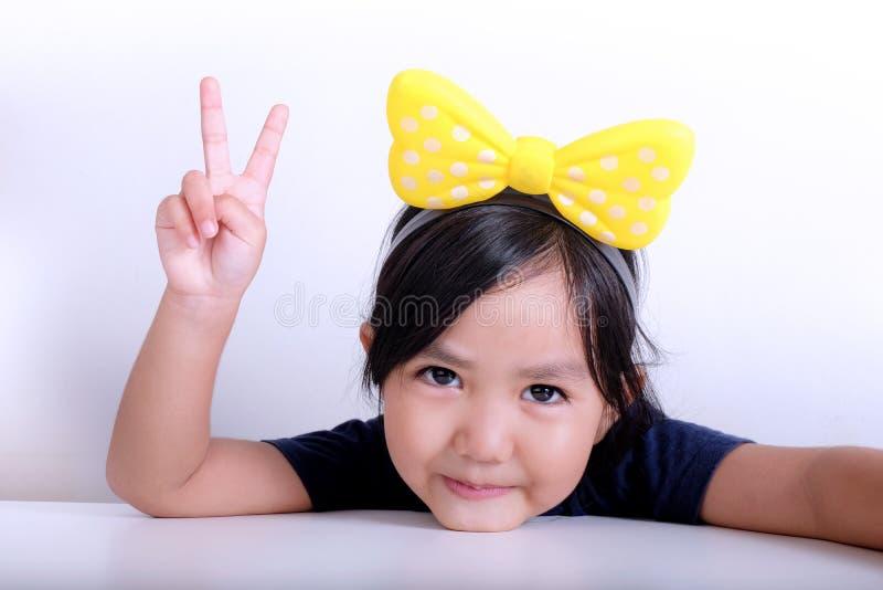 La chica joven muestra la muestra de la mano de la paz foto de archivo