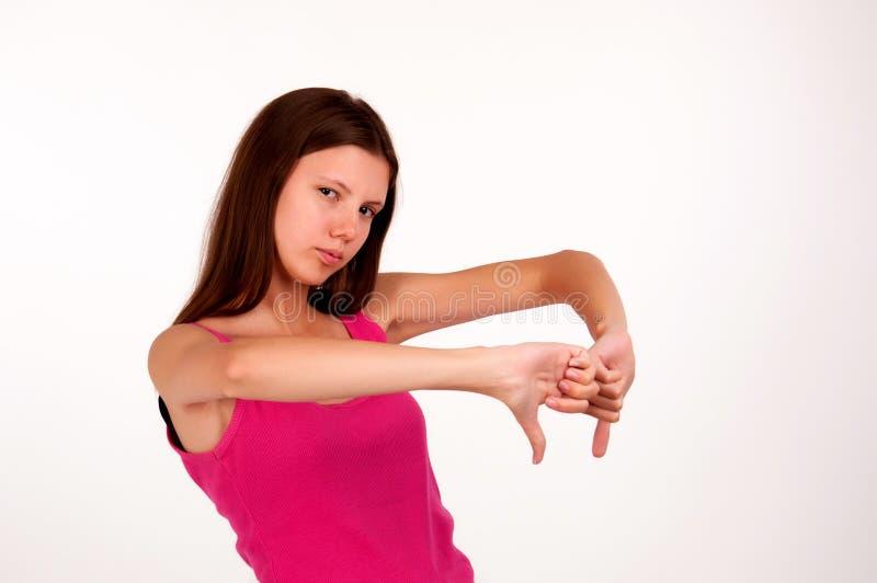 La chica joven muestra un gesto con su finger abajo aislado imagen de archivo