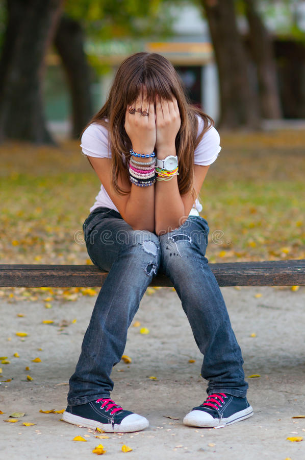 La chica joven oculta su cara con las manos fotografía de archivo libre de regalías