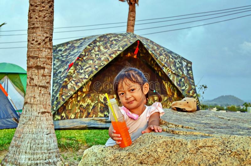 La chica joven ofrece su bebida anaranjada en un camping imagen de archivo libre de regalías