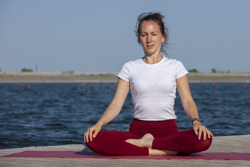 La chica joven practica la yoga en la orilla del lago, el concepto de disfrutar de la privacidad y de la concentraci?n, luz del s fotografía de archivo libre de regalías