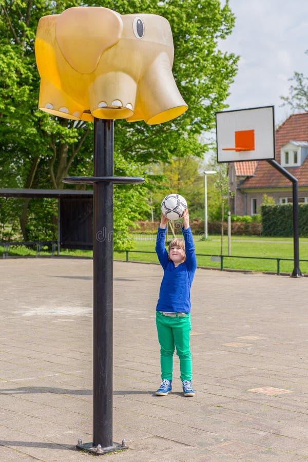 La chica joven que apunta la bola a la cesta le gusta el elefante fotografía de archivo